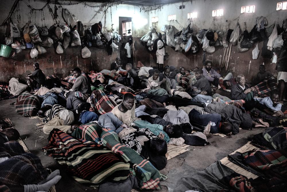 Prisioneros esperando autorización para salir a los espacios communes, después de 14 horas en la celda, en la prisión de Chichiri (Blantyre). El hacinamiento es un problema crónico en Malawi. En esta prisión de la imagen fue construida para unos 800 prisioneros, pero en la actualidad malviven en ella unos 2000. Foto: © Luca Sola / MSF