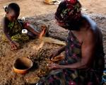 Una abuela y su nieta machacando la nuez de la palma aceitera para extraer el aceite y utilizarlo a modo de loción, en una zona interior de Togo. Copyright: Rafael Cabanillas.