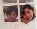 Dos niñas miran desde la ventana de una de las improvisadas tiendas que les sirven de alojamiento.