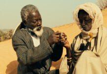 Fotograma de la película Hyenes, de Djibril Diop Mambety, restaurada por Metrograph. En la imagen, los dos protagonistas charlan, antes de que Ramatou ponga precio a la cabeza de Draman.